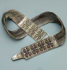 India | A Kerala silver belt, made of large double interlocking wire links, the buckle consisting of rectangular plates in openwork with red and blue glass stones. Weight 1100 g. | Around 1950. | Such arapatta were worn by Muslim women in Kozhikode (Calicut) || Est. 1'200€ ~ (June '13)