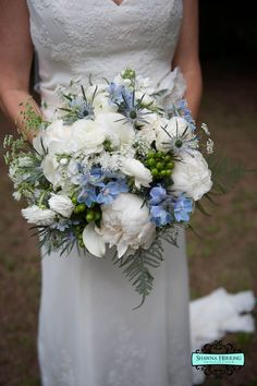 Rebecca's bouquet featured white peonies, mini callas, Queen Anne's Lace, Ranunculus, pale blue Delphinium, Eryngium and accented with green hypericum berries.