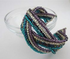 Memory Wire Cuff We've used 12 loops of bracelet memory wire, size 8 seed beads in 4 different colours and 270mm pieces of 0.8mm...