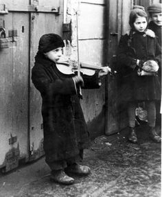 Warsaw, Poland, A child playing a violin in a ghetto street, February 1941.Sad to say they will be murdered in gas chambers