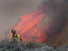 A firefighter monitors flames from the 213 Fire that broke containment lines on April 13south ofDurango, Colo.  Shaun Stanley, Durango Herald via AP