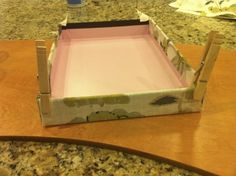 DIY fabric covered boxes, neat way to hold the edges till they dry, clothes pins