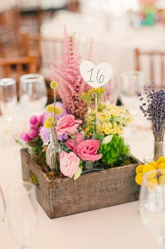 colorful wedding florals in wooden boxes.