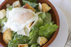 Poached Egg Caesar Salad   I love this salad! To me a warm runny egg over cool crisp greens with the yolk becoming enriched with whatever salad dressing you are using ............ Well, it just can't be beat in my book! Not only is it a rich, comforting meal - It's hella cheap!