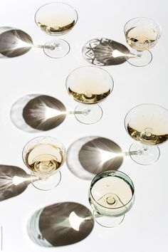 Champagne glasses with strong shadows by Pixel Stories for Stocksy United