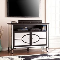 """Bowery Hill 52.75"""" Mirrored TV Stand in Black. High contrast never goes out of style, as seen here with this nod to mod media stand. Shimmering mirrors combine with the matte black finish to create a retro-inspired futuristic effect. A large media shelf effortlessly accommodates cable boxes, DVD players, or game consoles while adjustable interior shelves hold your movies and games with ease. Instantly glamorize your entertaining area with the addition of this old-Hollywood media stand...."""