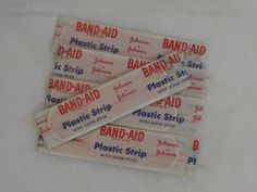 5 Vintage Band Aid Brand Plastic Strips with SUPER STICK.  1950s Era Vintage coolness.  Fill up those band-aid tins with period band-aids or use as props or in collages.  These are the nifty kind with real gauze and little red red strings to open them.