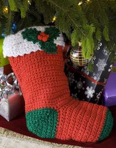 """Free crochet pattern. I made these for the boys this year but I used a main color they picked with cream accents. I also left off the cuff and the holly. They turned out so stinking cute! 2 strands held together took exactly 1 ball for each stocking of """"I love this yarn"""" for the main color. 1 ball cream for 2 stockings"""