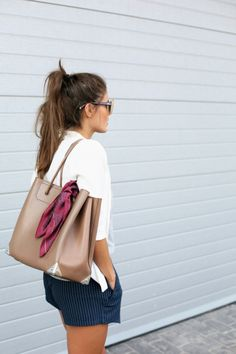 Tie a scarf to a neutral bag to give it a more expensive look