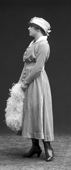 Young woman in velvet dress and ostrich feather fan, 1915.