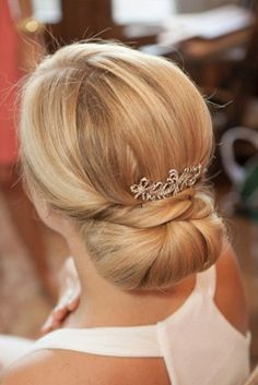 Low bun with brooch and beautiful white dress