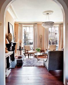 Living room. Peach wall. Cream curtains. Arched entry. Wooden floor. Modern chandelier.