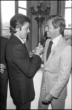 Alain Delon serre la main de Jean-Paul Belmondo quand celui-ci est récompensé à Paris en 1980