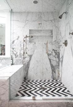 An large glass door entryway enhances the black and white, mixed pattern appeal of this shower enclosure.