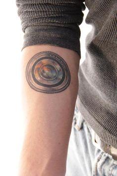 Camera lens tattoo.  I like the watercolor style.