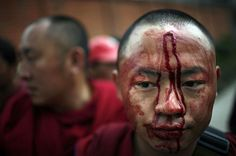 simply-war:    Blood flows from the forehead of a Tibetan monk beaten by police during a peace rally in Kathmandu, Nepal.Photography by: Brian Sokol / The New York Times / Redux