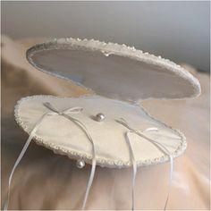 "WeddingDepot.com ~ Ring Bearer Pillow - Chiffon Shell -  Ivory ~ ring ""pillow"" is configured like an shell that opens to reveal the rings inside. The exterior is covered with pleated tulle and accented with rhinestones, beads, and pearls."