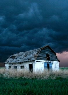 Aged with beauty - Old abandoned farm house under blue storm cloud