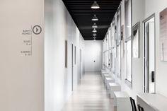 Monochrome corridor inside the Taller De Musics music school by Dom Arquitectura.