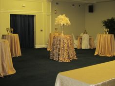 Cocktail hour setup with coordinating tablecloths, a mix of high-top cocktail tables and intimate seating, decorated with candle holders, and feather arrangements.
