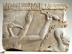 An ancient Egyptian sandstone cornice block, 41–68, with relief showing the baptism of pharaoh; the ibis-headed god Thoth pours water, symbolised by streams of ankhs (life symbols/hieroglyphs) over the head of the pharaoh. (Metropolitan Museum of Art)