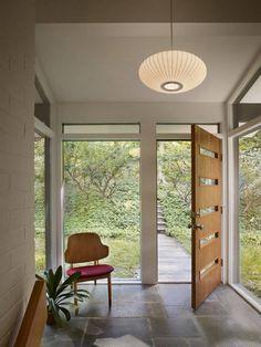 Midcentury modern home entrance - stone floors - textured walls - ceiling pendant