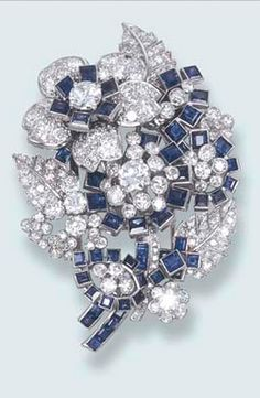 AN ELEGANT SAPPHIRE AND DIAMOND FLORAL BROOCH, BY CARTIER Designed as a circular-cut diamond and square-cut sapphire bouquet, mounted in platinum, 5.5 cm. long, with red leather Cartier case Signed Cartier, London
