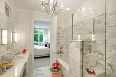 En suite bathroom features a crystal chandelier hung over a West Elm Martini Stool placed on statuary marble floor tiles in front of a marble clad drop-in bathtub finished with a nickel tub filler fixed beneath a niche framed by gray and white marble beveled subway surround tiles.
