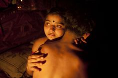 "Seventeen-year-old prostitute Hashi, embraces a Babu, her ""husband"", inside her small room at Kandapara brothel in Tangail, a northeastern city of Bangladesh"