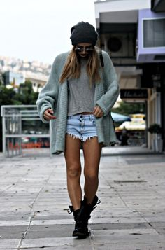 cut off shorts paired with a simple tee and an open longsleeved sweater topped with a grey floppy beanie and combat boots