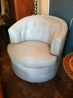 This pair of vintage barrel club chairs are upholstered in a beautiful sea foam green fabric. Custom made with button detailing, these adorable chairs spin!