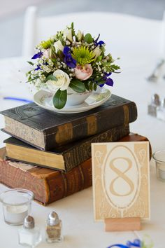 Vintage books elevate a a teacup and saucer floral arrangement (Photo by Aaron Watson Photography)