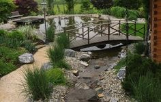 This Asian inspired bridge and water garden was created to fill an odd spot in the corner of a property. It extends the view and gives this landscape a sense of adventure!   Creating journeys within your landscapes, such as trails and bridges, extends the space and creates more interest.