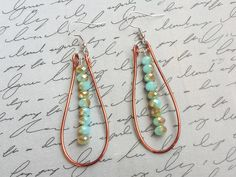 Lovely Copper Wire Dangle Earrings with a beautiful Turquoise colored beads that have Gold Accents. Accented with Silver Hooks. -------------------------------- The earring wires are nickel free fishhook style. -------------------------------- These earrings measure 3 inches from top of fishhook wire to bottom. -------------------------------- These earrings would make a wonderful gift for any occasion! Get your special someone something they will adore…