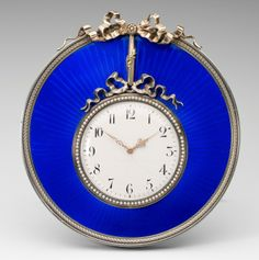 Fabergé clock, of circular form and guilloché enamelled in blue, the dial of this clock appears to be suspended from a bow, which itself is suspended from a bow surmounting the top of the clock. It is decorated with a bezel of seed pearls. Workmaster Victor Aarne, 1908. Acquired by HRH Prince Philip, The Duke of Edinburgh, at the time of his marriage, 1947.