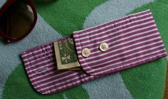coin purse made from the cuff of an old menswear shirt - cut off cuff - Fold cuff in half so that the buttonhole side is longer than the side with the button. The longer side should fold over and the button hole and button should meet. Pin in place. Stitch the sides closed.  Opens at buttons to create small pocket.  Would fit a USB drive or girl things.