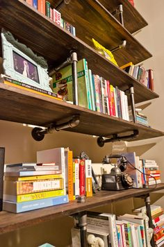 Look carefully and you will see industrial pipe has been used to make bookshelves.  What a clever idea for a plumbers office or den.