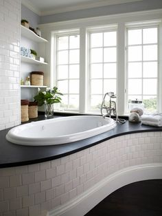 A curved surround topped with slate sets the stage for a luxurious soaking tub. A unique design like this one adds architectural interest to a bathroom, and a wide countertop-like space around the tub provides a spot for towels and bottles of bubble bath. House Styles, Bathtub Design, Bathroom Decor, Home, Gorgeous Bathroom, Bathroom Design, Beautiful Bathrooms, My Ideal Home, Small Bathroom Decor