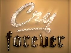 Open-face channel letters with incandescent light bulbs. The play between script and gothic fonts create a dramatic flair which is further enhanced by the stunning glow effect of the lights.