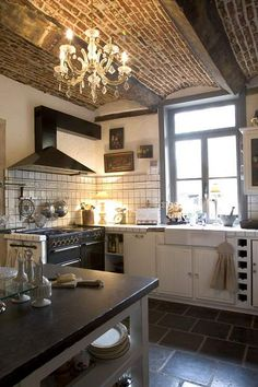 I want this kitchen. Love the juxtapo of the glass chandelier and brick on the ceiling.