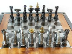 French designer Eric Claverie used recycled hardware pieces to craft his unusual set. He built the board from small sheets of brushed steel then painted. He added adjustable feet to raise it up. For his pieces, he used discarded nuts, tubes, & bolts that he polished, varnished, & welded together to create robotlike bishops, knights, & rooks. Some sport blue balls for eyes; the pawns resemble tiny vacuums. The crowns adorning Claverie's kings and queens are assemblages