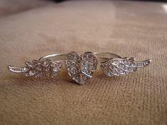 """Anel em metal prata com o símbolo """"Paz e Amor"""" no formato de coração e asas. Aplicação de strass Swarovski branco.  Aros 17 (diâmetro: 1,72cm) e 18 (diâmetro: 1,75cm) R$45,00"""