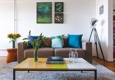Sala de estar com decoração mais masculina que inclui sofá cinza, mesa de centro com três cores e almofadas em tons de azul.