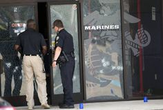 Police officers enter the Armed Forces Career Center through a bullet-riddled door after a gunman opened fire on the building Thursday, July 16, 2015, in Chattanooga. Authorities say there were multiple casualties including the gunman. Photo by Associated Press /Times Free Press.