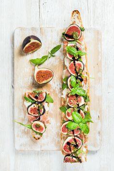 Long baguette sandwich with prosciutto, mozzarella, arugula, figs and basil - Stock Photo - Images