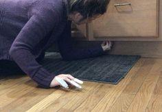 Mom sticks command hooks under her kitchen cabinet for a genius trick
