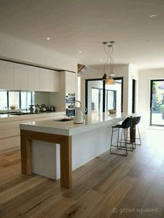 Summer style!! White and pale wood! Modern contemporary kitchen with wood floors and white cabinets! Gorgeous long kitchen island! Lots of light from lots of windows - even windows along the backsplash! Cool and fresh!