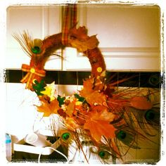 made this wreath today its my 3 layer leaf wreath first layer is leavess that i cut out of paper that my son colored on the second layer are feldt leaves and the third layer are real leaves from my yard preserved in wax to save their colors and then i added some dry colored grass, fake acorns, buttons and ribbon and tossed in a few peacock feathers :D