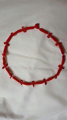 Girocollo composto da piccoli tubolari alternati a fiocchetti.  La lunghezza è circa 35 cm, arriva sotto la gola. Il colore è rosso ma si può scegliere. Il costo è di euro 7.