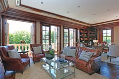 A mahogany-clad office has built-in bookshelves and a balcony overlooking the pool.